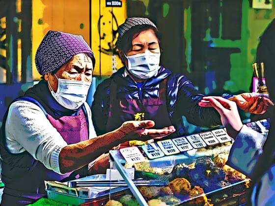 women wearing masks selling items