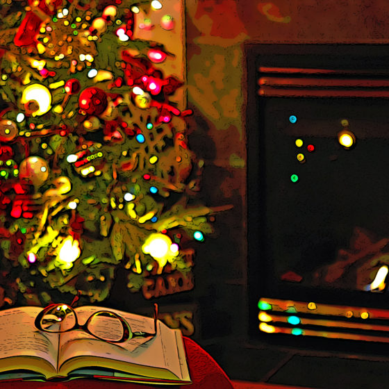 Reading glasses resting on top of an open book in front of a fire place and a Christmas tree