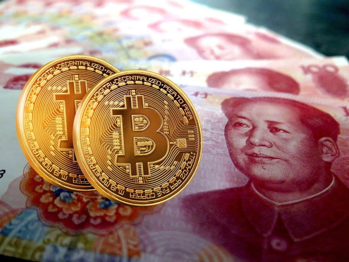 Bitcoins in front of 100 RMB bills
