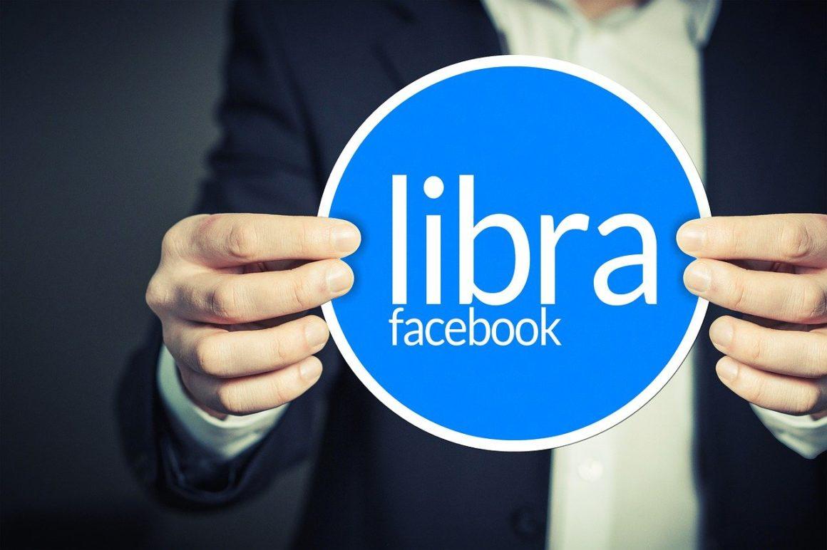 Man holds blue circular sign of Facebook's LIbra