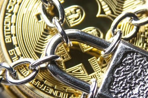 Visualisierung eines durch Ketten und ein Vorhängeschloss gesperrten Bitcoin