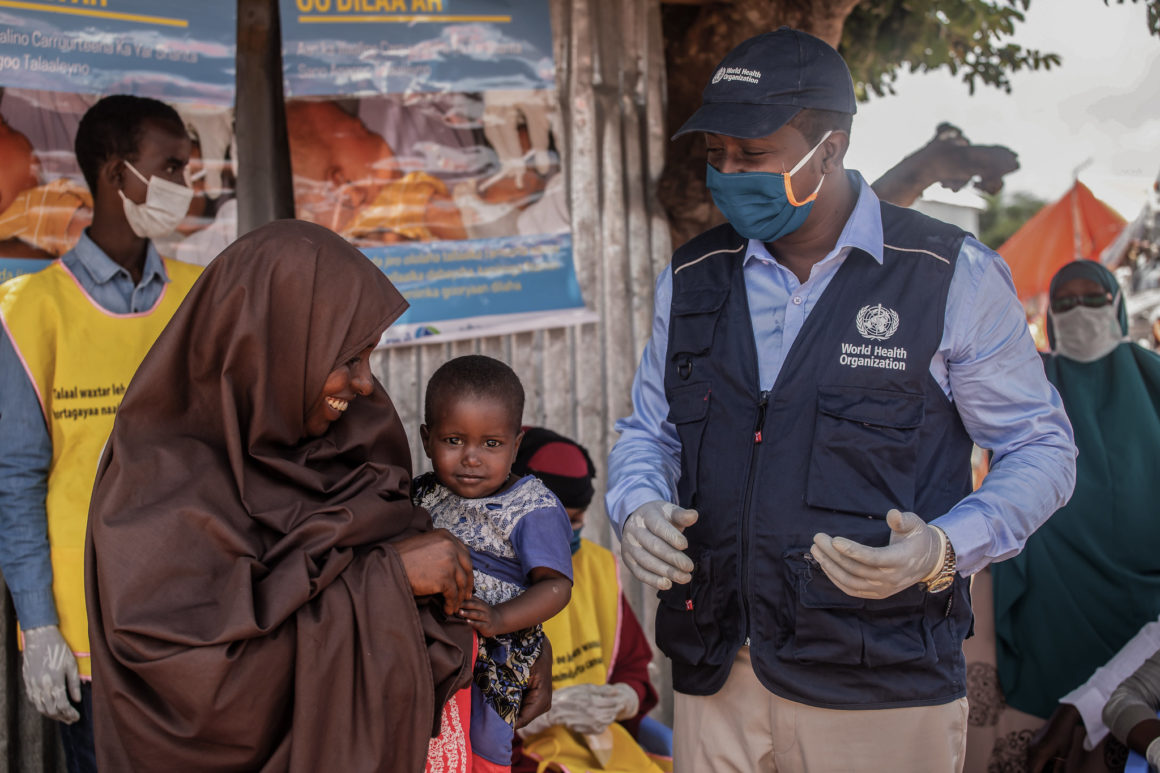 A staff of the World Health Organization (WHO) talks to a mother during an immunization exercise in Kahda district of Mogadishu, Somalia on September 1, 2020