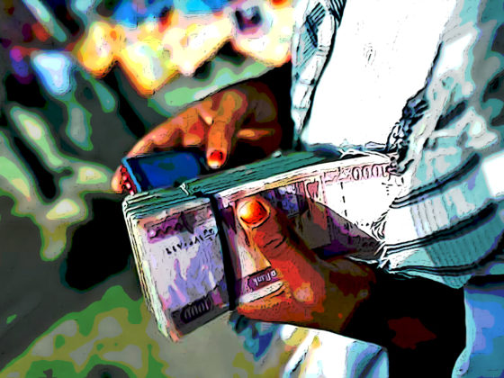 Person holds a bundle of money while using mobile phone