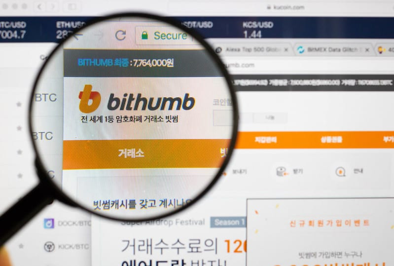 Magnifying glass above Bithumb website