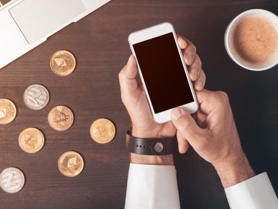 Man using phone with coffee and model cryptocurrency coins on table