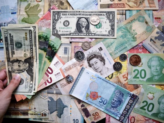 World currencies scattered on a surface as central banks around the world collaborate on CBDC developments