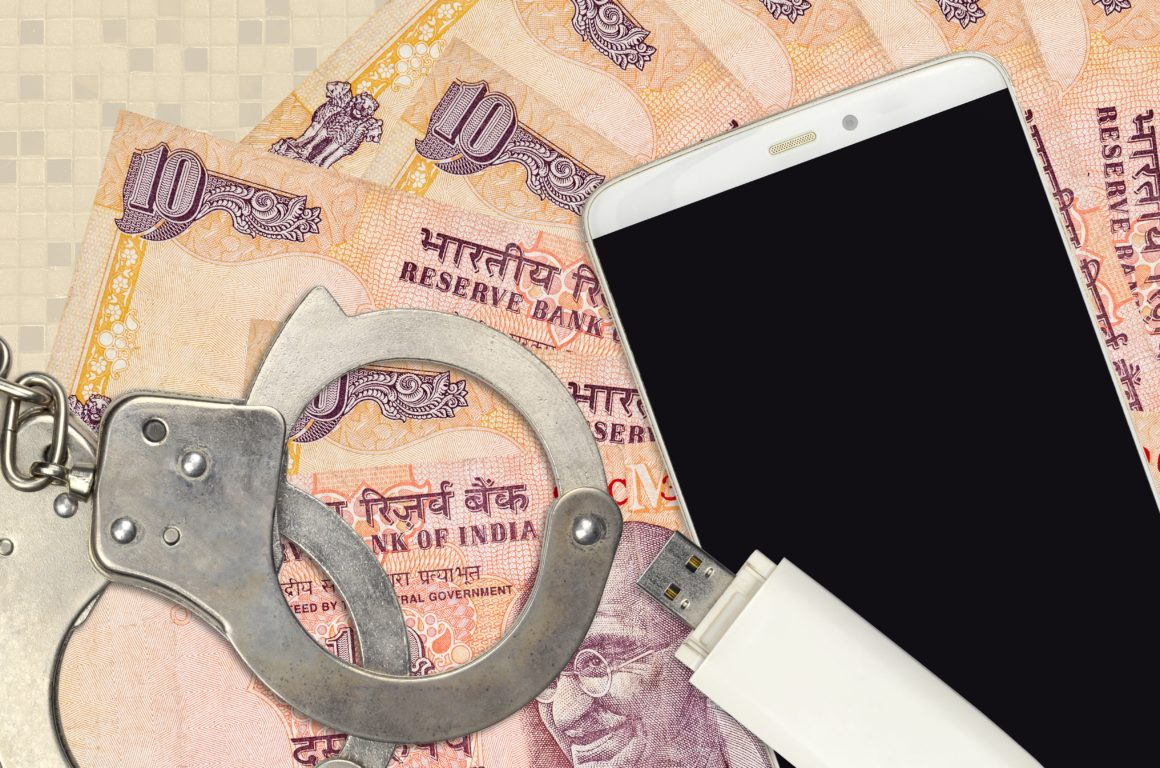 10 Indian rupees bills and smartphone with police handcuffs. Concept of hackers phishing attacks, illegal scam or malware soft distribution