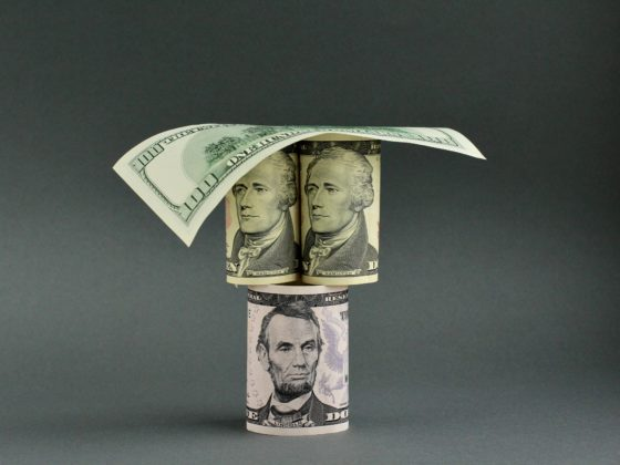 Rolled US dollar bills stacked in the shape of an inverted pyramid