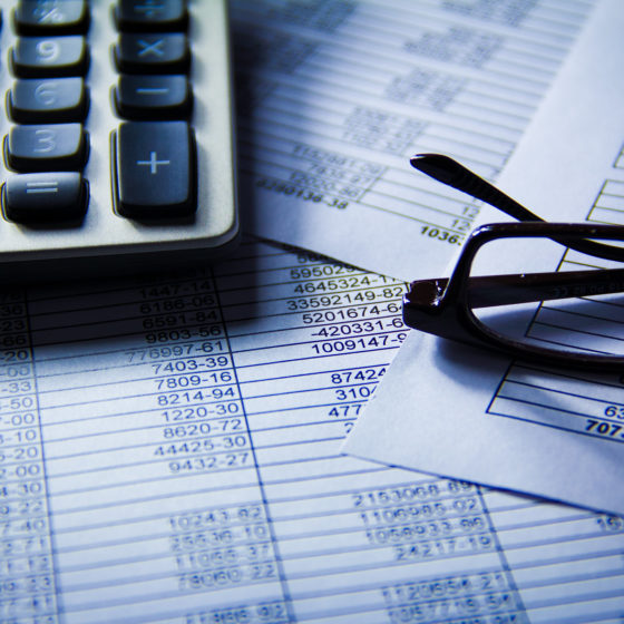 Glasses and calculator on top of spread sheet as decentralized finance sets to take off