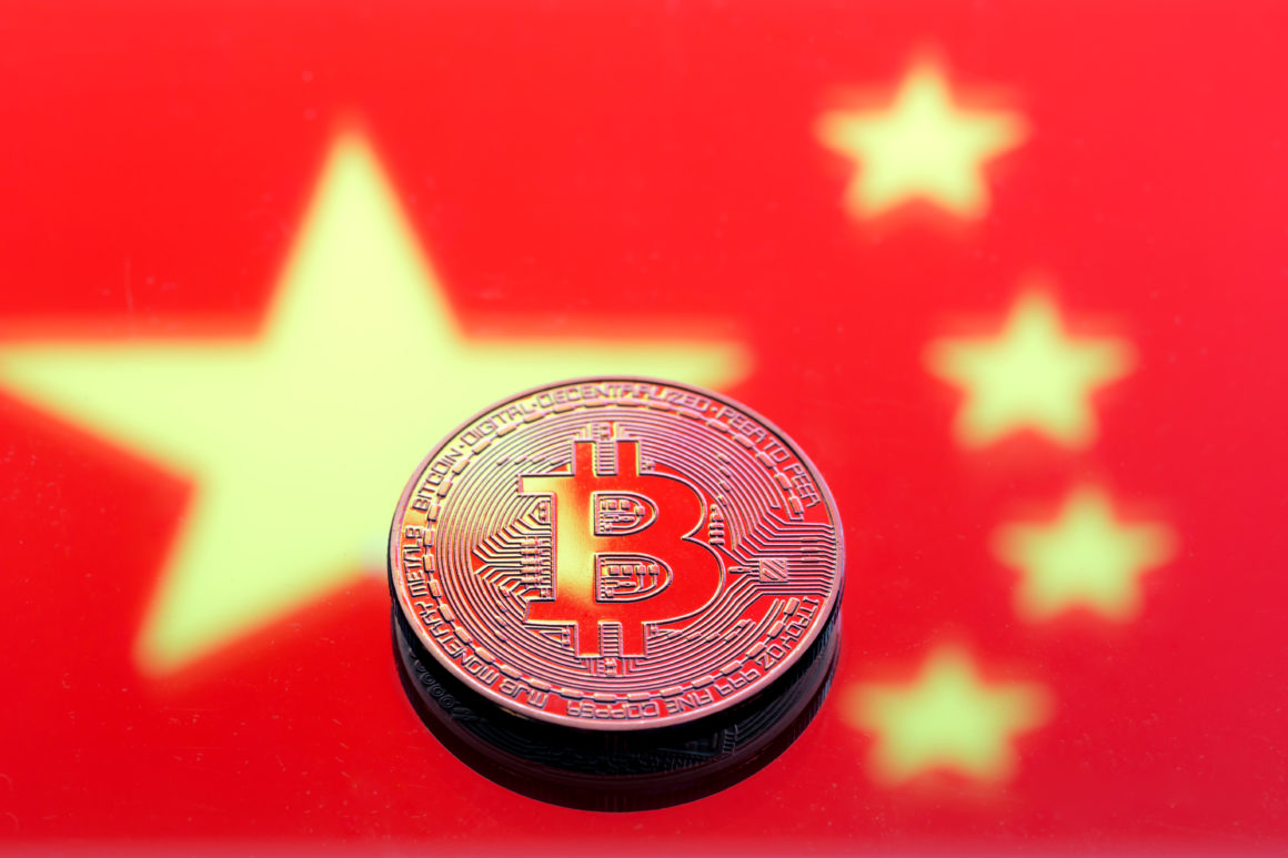 coins Bitcoin, against the background of the Chinese flag, concept of virtual money, close-up. Conceptual image of digital crypto currency.