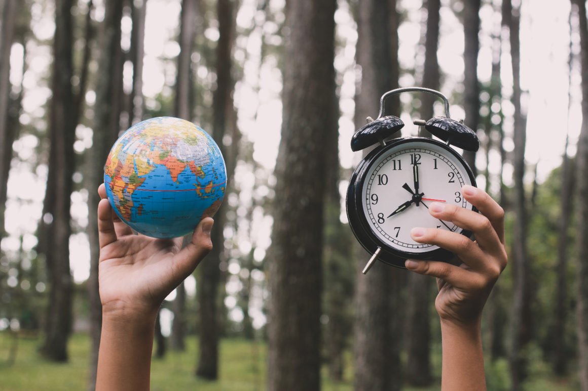 Hands holding a globe and alarm clock with forest in the background. Earth Hour and sustainability — green bonds