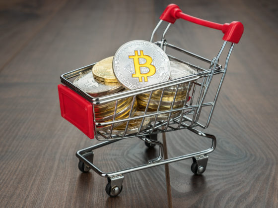 shopping trolley full of bitcoin currency concept on the wooden background