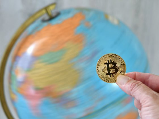 Picture of person holding a physical rendition of a Bitcoin while spinning globe behind the back is positioned at China