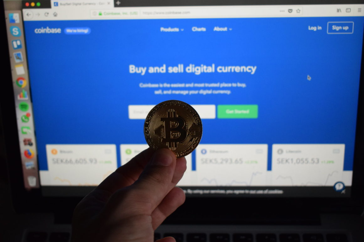 Holding a Bitcoin in front of Coinbase website on PC monitor