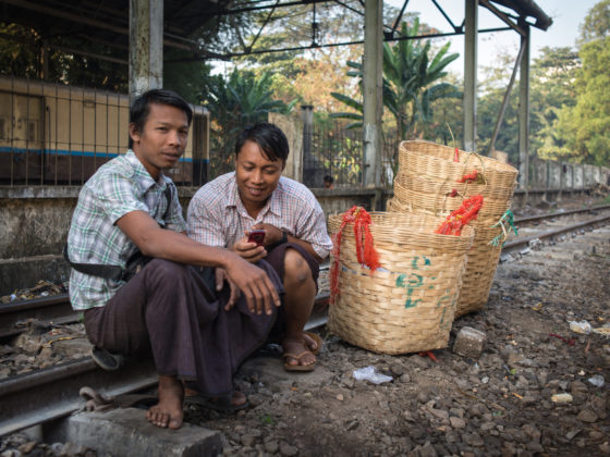 Basket salesmen play with a mobile phone as they squat on the tracks and wait for the Yangon Circle Line train