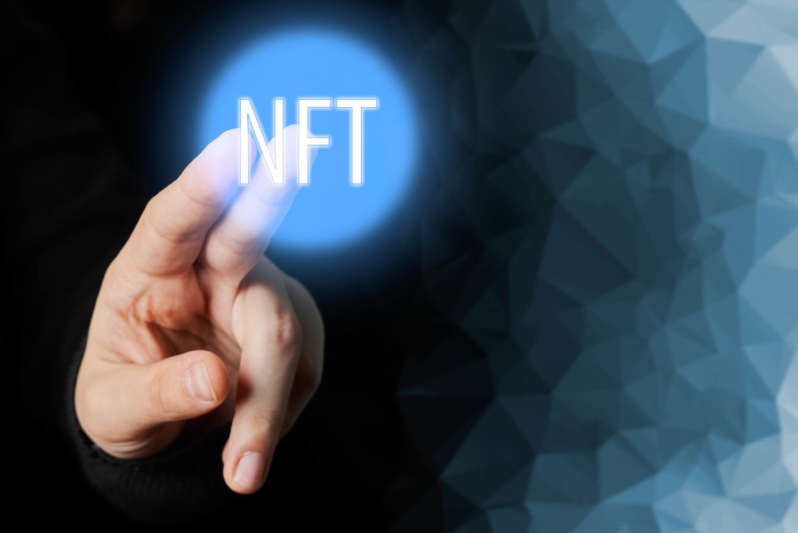 Fingers pointing to the words NFT or non-fungible tokens. An NFT is a unique, non-interchangeable digital asset whose authenticity and true ownership is tracked on a blockchain