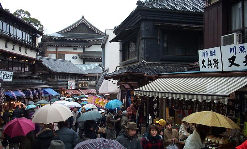 Crowd of people holding umbrellas on the streets of Narita Japan