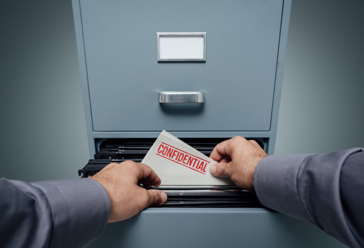 Man grabs confidential documents out of a cabinet. Blockchain data privacy