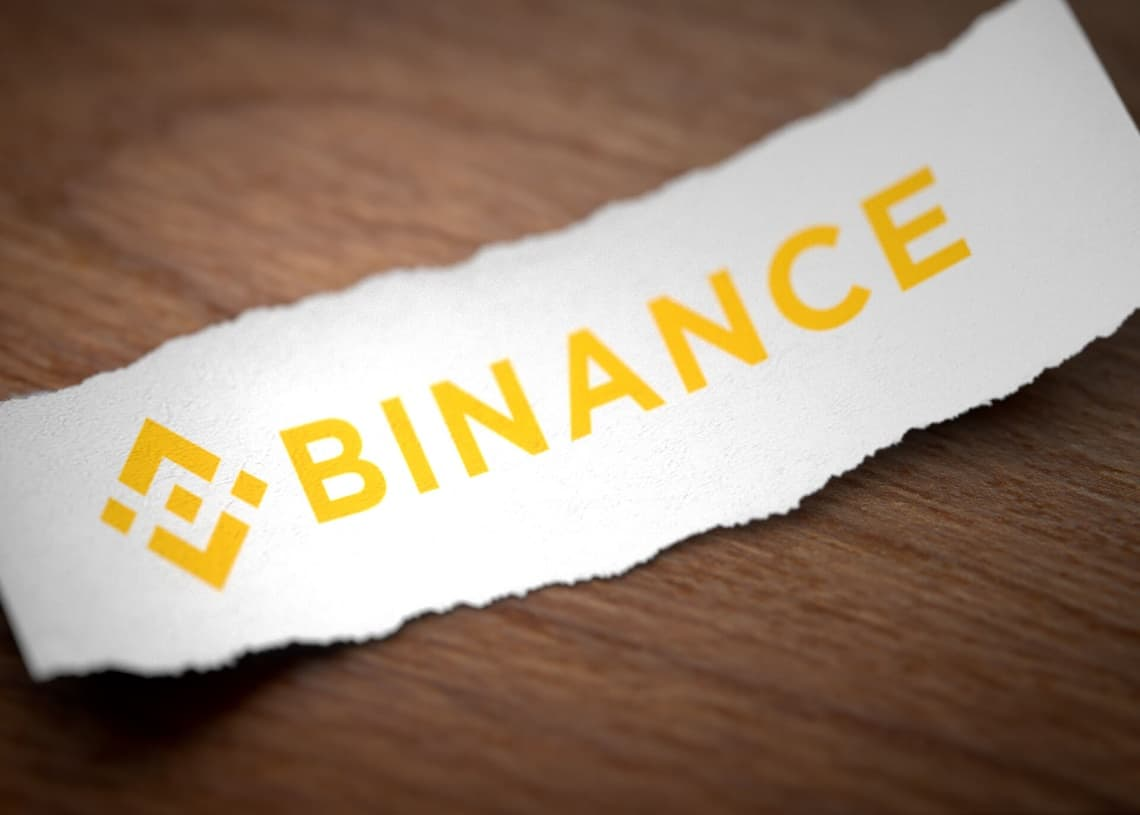 Binance logo on a torn strip of paper