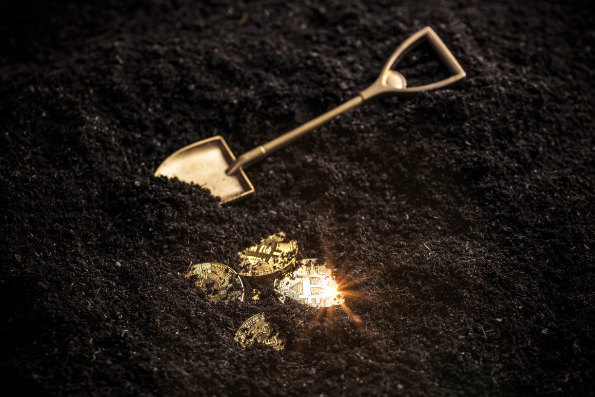 Golden bitcoin mining from the soil with shovel