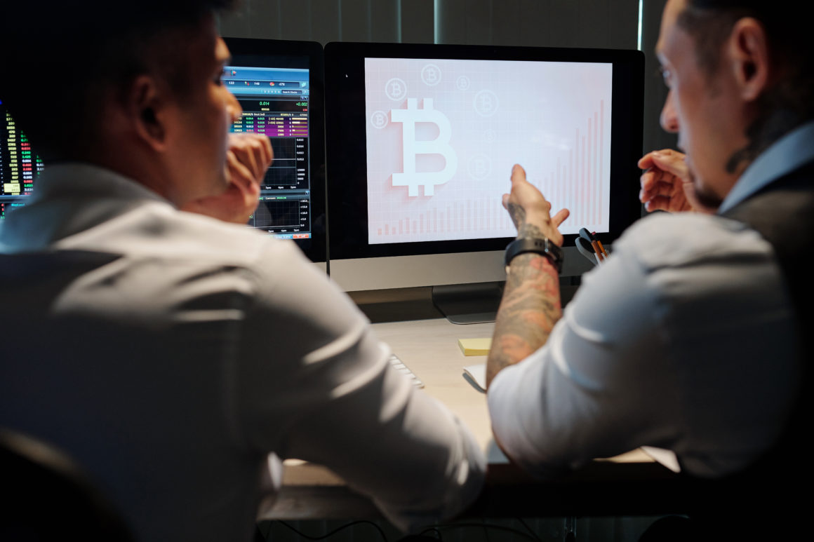 Brokers trading bitcoin in front of computer monitors