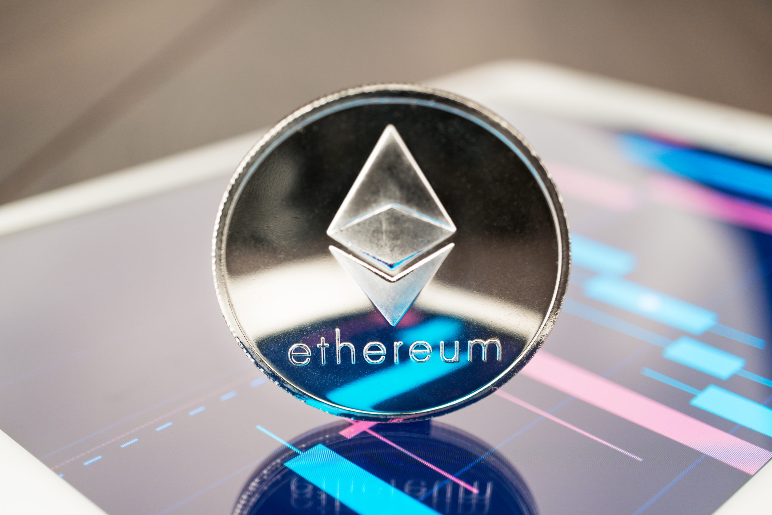 close-up photo of ether cryptocurrency physical coin on the tablet computer showing stock market charts.