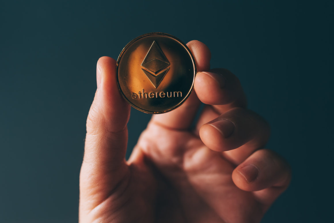 Ethereum cryptocurrency in hand, blockchain technology decentralized currency coin