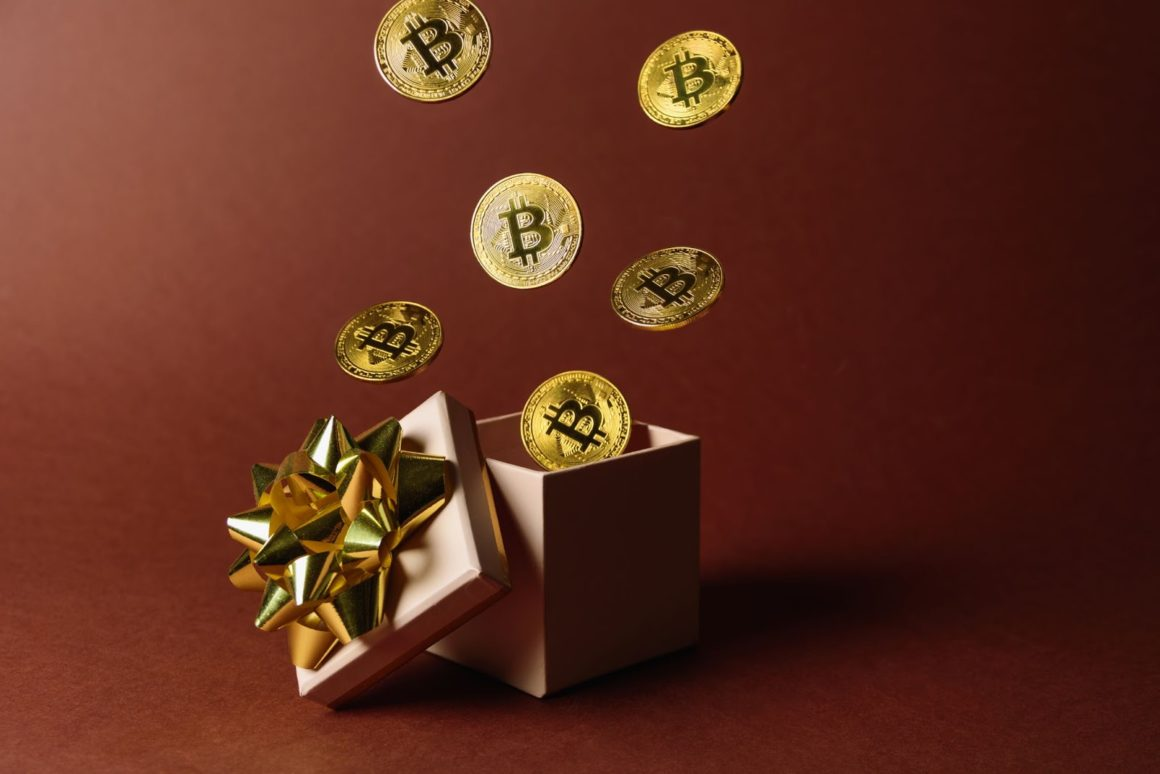 Physical Bitcoins flying out of a gift box