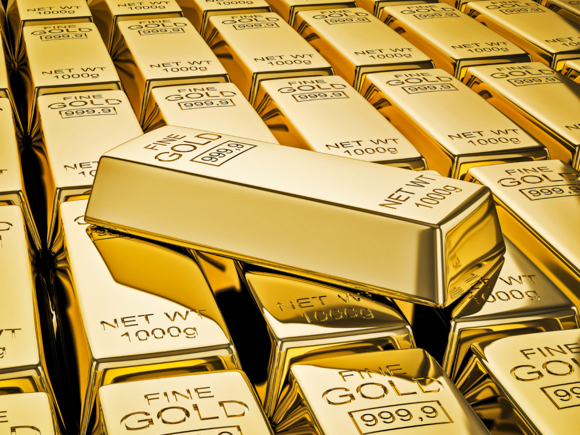 Gold bar on stacks of gold bullions close up | Gold vs. Bitcoin: Which one is better as as a safe-haven asset?