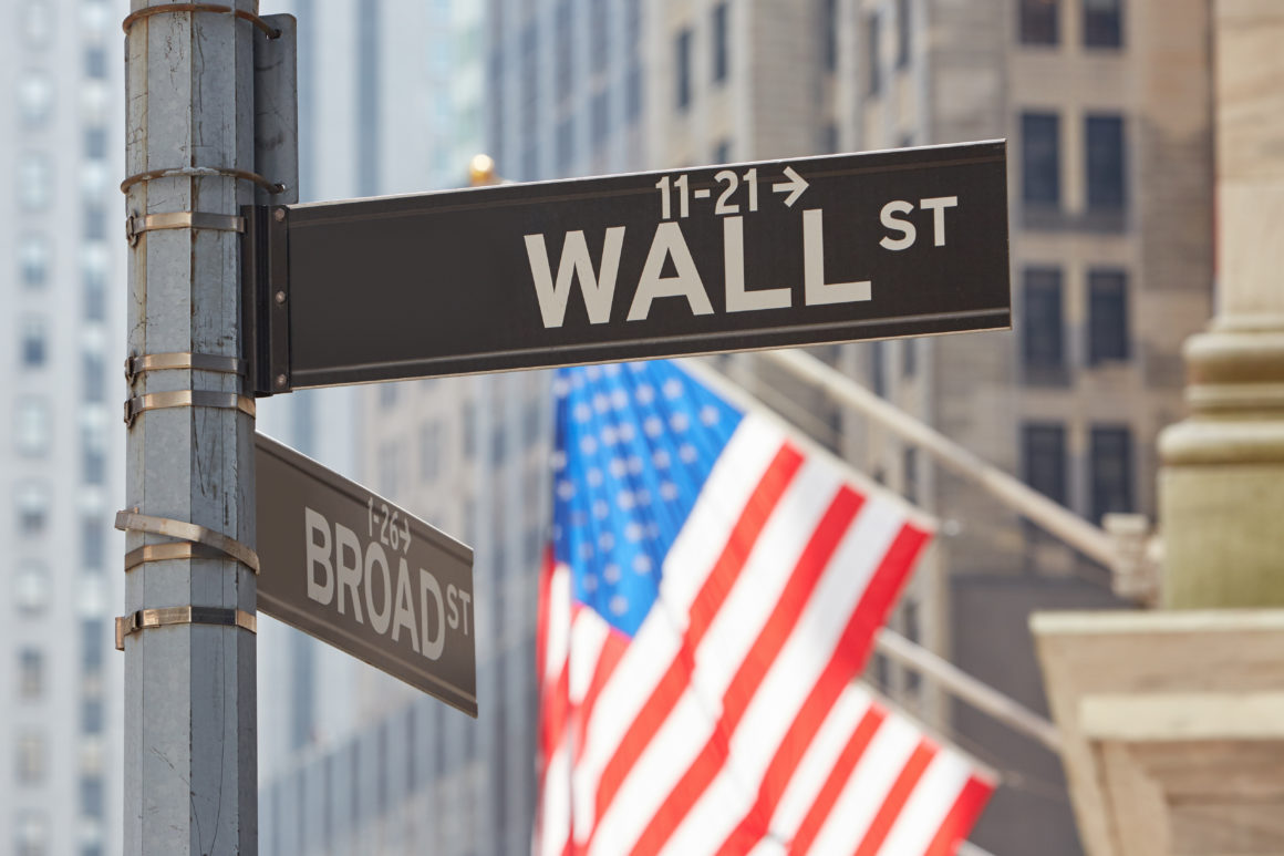 Wall Street sign near Stock Exchange with US flags, financial di