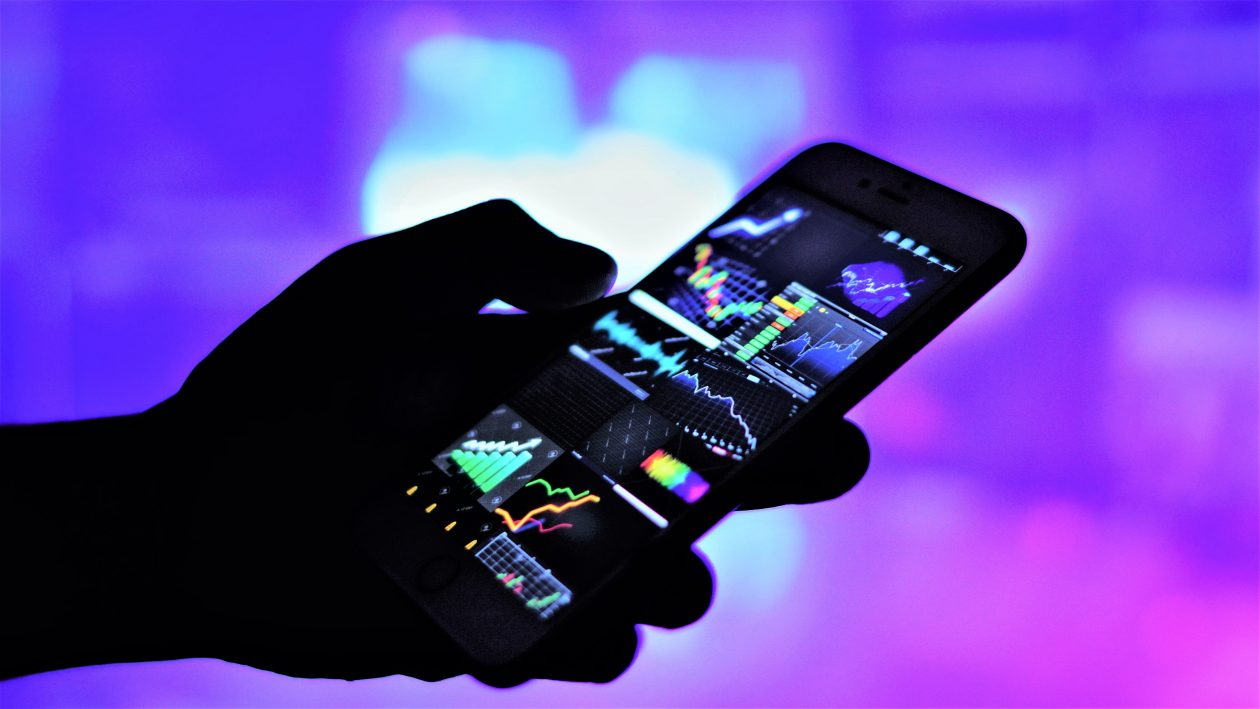 hand holding mobile and graphs of currency exchang GHL7BNR