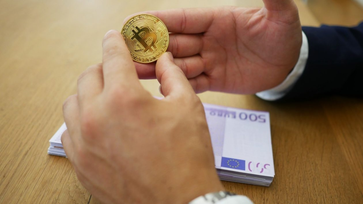 Hands holding a Bitcoin crypto with Euro notes on the table