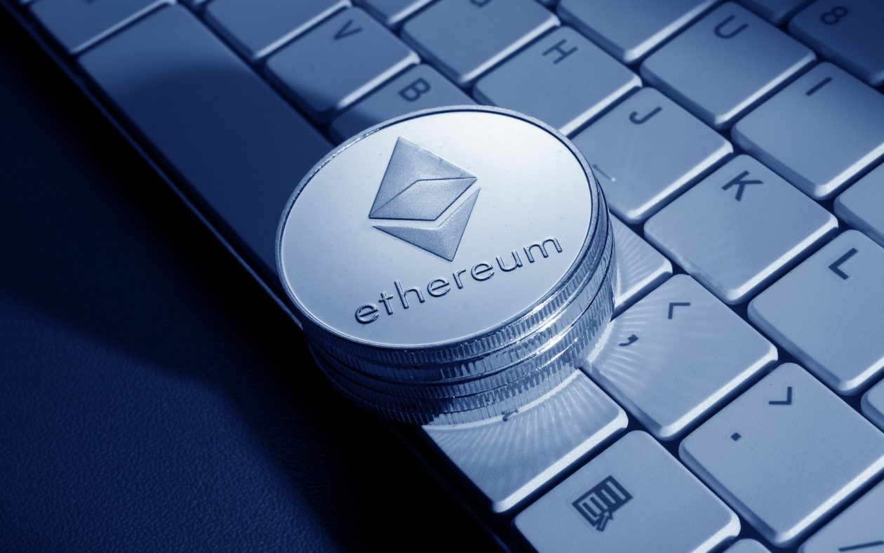 Ethereum Ether cryptocurrency coin on a keyboard