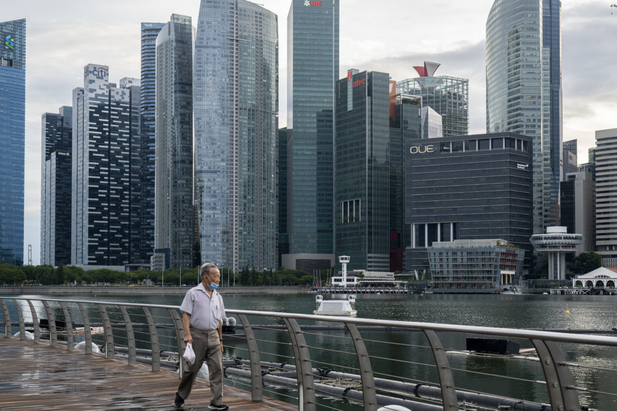In Singapore, man wearing a protective mask walks past the Marina Bay Sands Shopping Center with the central business district in the background
