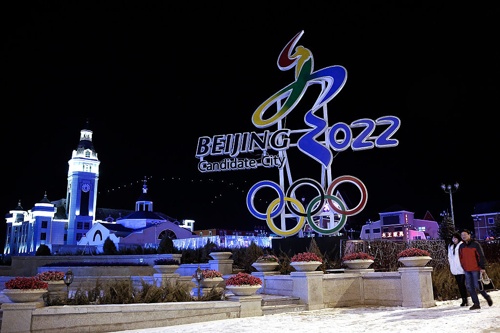 BEIJING, CHINA - JANUARY 16: Chinese citizens walks past a a sign for Beijing's bid for the Winter Olympics logo on January 16, 2015 in Zhangjiakou, Hebei Province, China. 2015 is Beijing's 2022 Winter Olympics bid to kick off the new year. (Photo by Lintao Zhang/Getty Images)