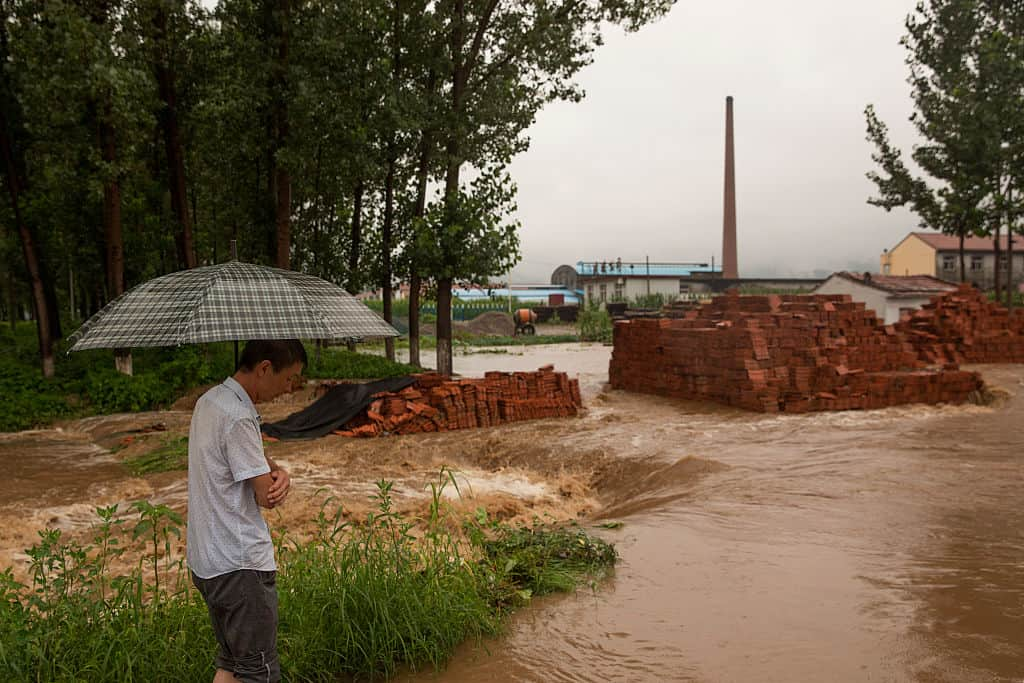 A man looks at flood waters surrounding his village on July 19 in Linzhou, Henan Province. Torrential rain has caused severe flooding in Northern China, leaving at least one dead and 34 missing. (Photo by Lintao Zhang/Getty Images)