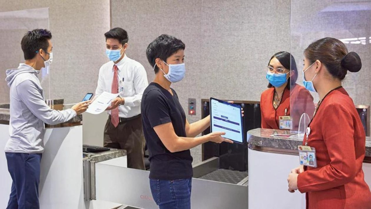 Temasek and Affinidi representatives Nicholas Foo (leftmost) and Gina Chiang (middle) engaging SATS staff on the Affinidi Unifier app, ahead of roll-out by airlines onboarded by Changi Airport Group