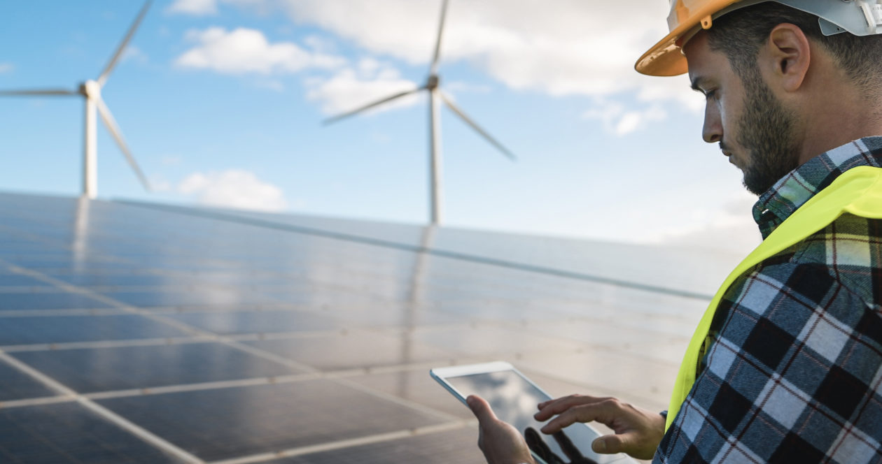 Man adjusting parameter in font of renewable energy facilities, clean energy boost crypto mining stocks