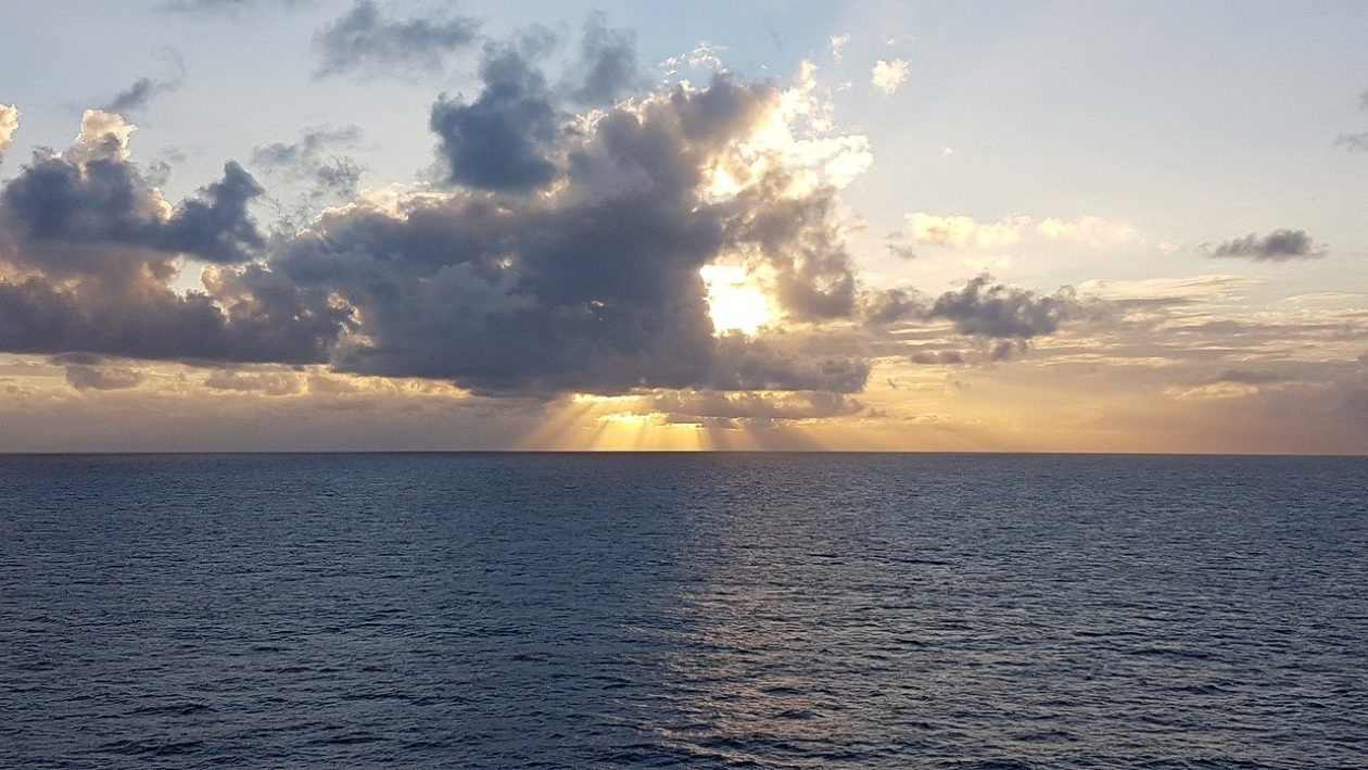 Sun shining behind clouds above the sea