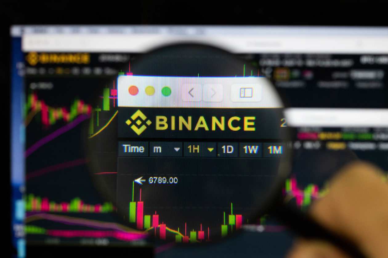 Magnifying glass zooming in on cryptocurrency exchange Binance logo on trading platform
