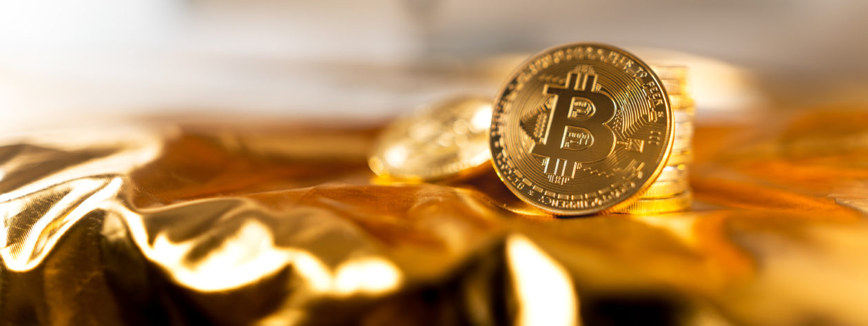 bitcoin on golden background, crypto vs gold, Which is more worth investing in cryptocurrency or gold