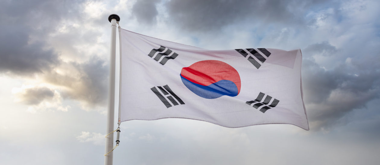 """South Korean national flag on a pole waving against cloudy sky background 