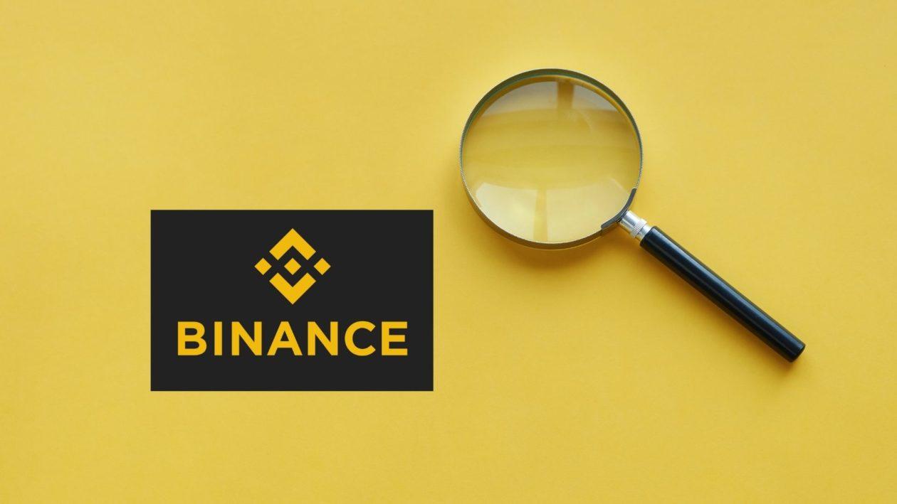 Crypto exchange Binance logo with magnifying glass