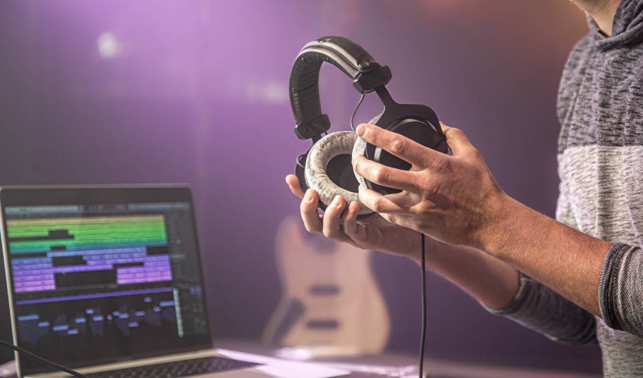 Studio audio headphones for recording sound in male hands on a blurred studio background of a music studio. Sound recording process.